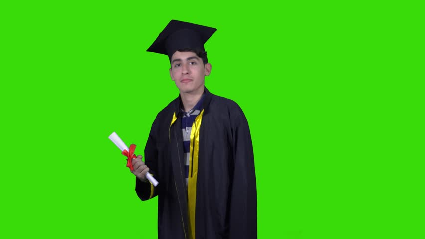 Smiley student wearing the graduation robe and cap holds rolled certificate looking directly at the camera green Chroma.