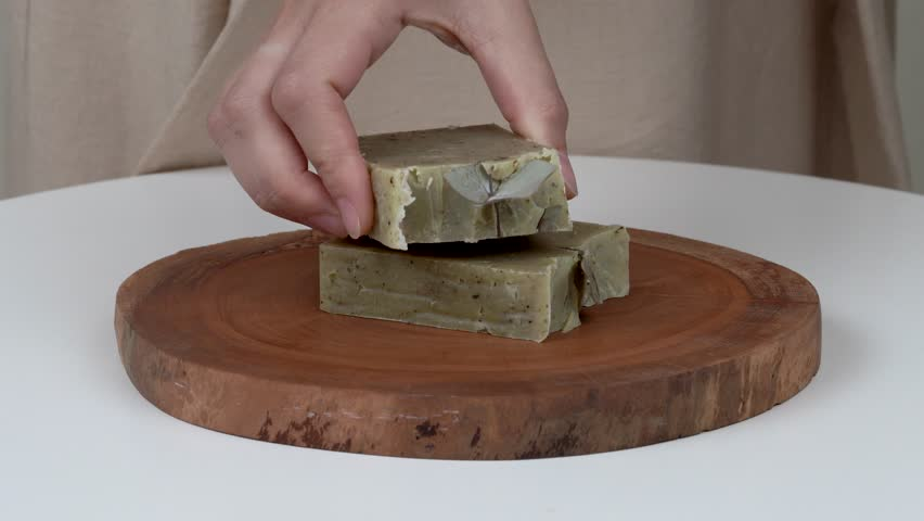 A close-up of woman's hands putting bars of natural lavender soap on a round wooden tray. On the top she puts two bars with lavender and eucalyptus.
