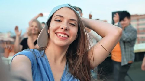 Close-up face of young woman in cap taking selfie surrounded by friends at rooftop party
