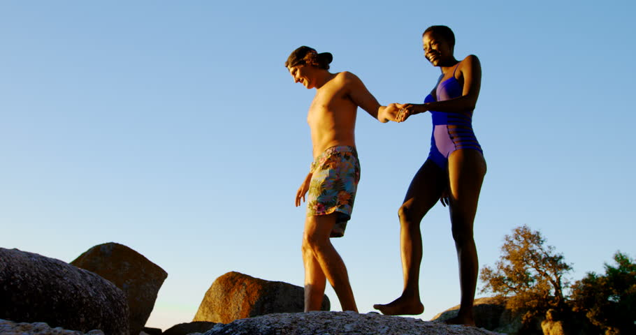 Couple walking hand in hand on the rock at beach 4k | Shutterstock HD Video #1014379328