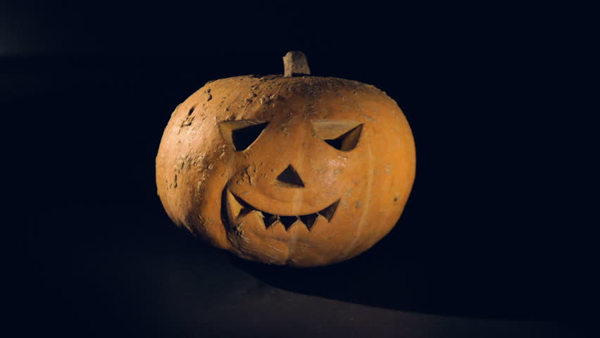 Smoke is getting ejected and then dissipating around a jack-o-lantern. Scary carved halloween pumpkin. | Shutterstock HD Video #1014381278