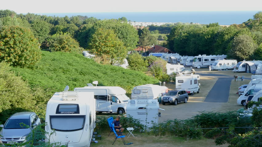 NORFOLK, ENGLAND, JULY 24TH, 2018: Early evening at sundown, pan across a peaceful campsite of parked caravans and motorhomes, surrounded by trees, during a long UK heatwave.