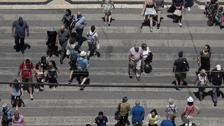 Pedestrians Crossing Street Zebra Sign Top View. LISBON, PORTUGAL - 13 JUNE 2018; Aerial view of a pedestrian crossing in a busy street with many people. | Shutterstock HD Video #1014429308