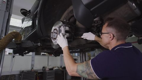 Car mechanic cleans the dust shock absorbers of the car.