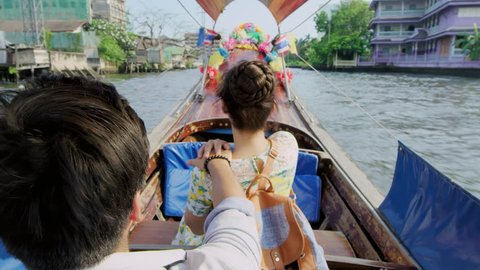 Asian tourist couple having an intimate real romantic love moment on tour longtail boat, on the chao phraya river water way  villages in Bangkok, Thailand. Slow motion