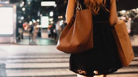 Close-up view of young stylish woman with shopping bags crossing road in new York, America downtown in the evening.