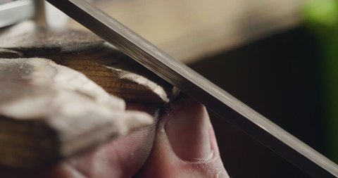 Macro of a goldsmith cutting and filing the steel to make a ring. Concept: silver, style, production