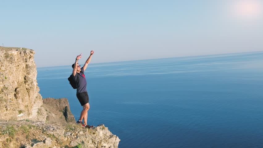 Male backpacker traveler approach to precipice enjoying and making gesture of winner raising hands #1014514388