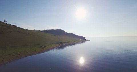 Drone flies along the stony shore o a Baikal lake