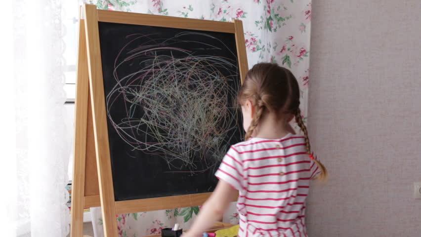 Little Preschool Girl Writing on Blackboard. Toddler girl holding chalk and drawing.   Shutterstock HD Video #1014552278