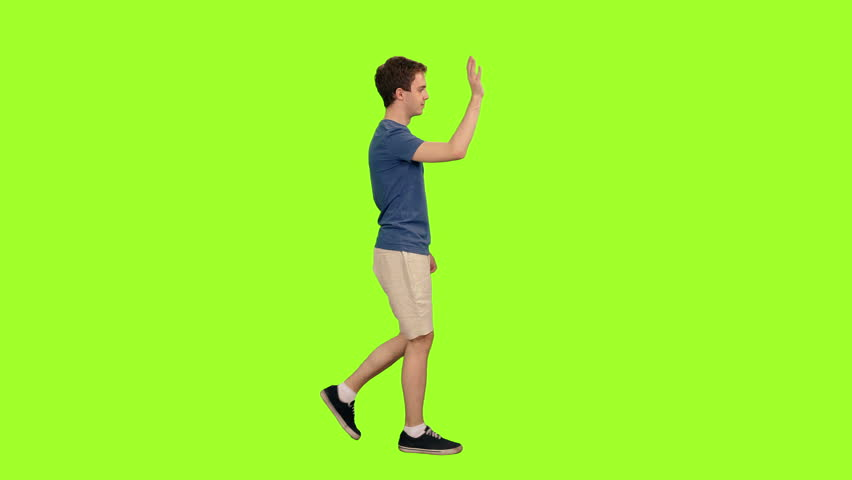 Handsome student waving hand hi while walking on green chroma key background, Side view, 4k pre-keyed footage #1014559778