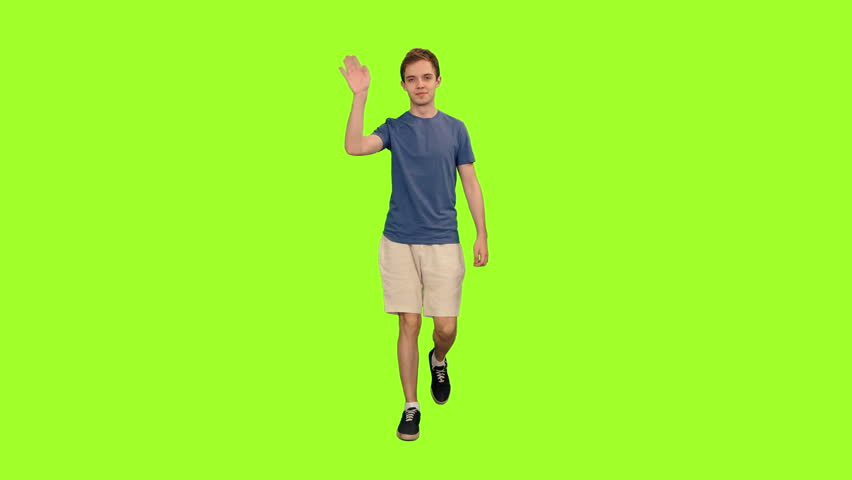 Young attractive student in blue T-shirt and light shorts waving hand hello while walking on green screen background, Chroma key, Front view, 4k pre-keyed footage