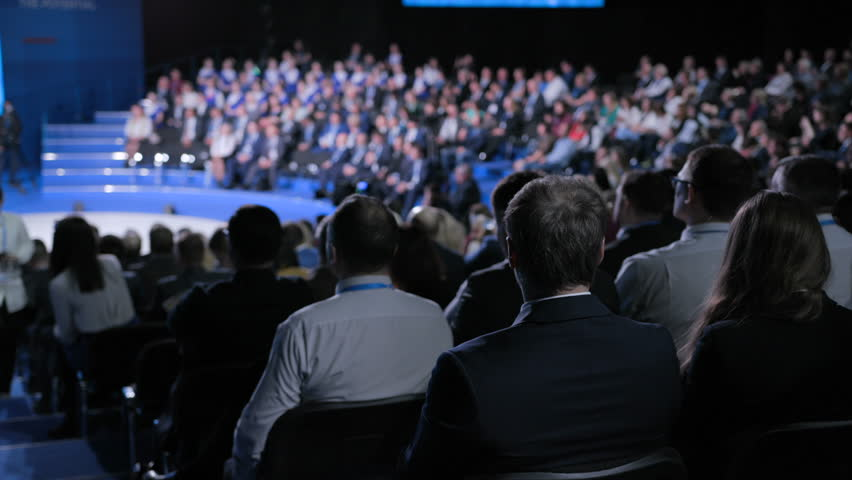 Confident official team at crowded economic forum for strategy education. Concept of male partner or politician at trading briefing indoors. Full row of seats in large place for listener or spectator   Shutterstock HD Video #1014561968