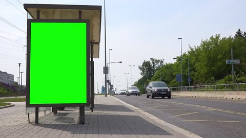 Green screen on the side of a bus stop in an urban area