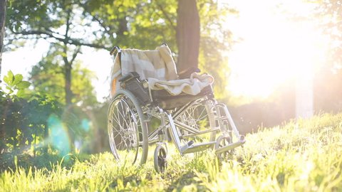 steel empty wheelchair with blanket standing on green grass in summer park with sun shining brightly on background healthcare concept physical rehabilitation injury prevention wheelchairs accessible