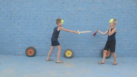 Children learn to fight with weapons in their hands. Woman shows combat techniques with swords. Boys dream of adventures, victories, travels, exploits. Conceptual preparation of spirit, patriotism