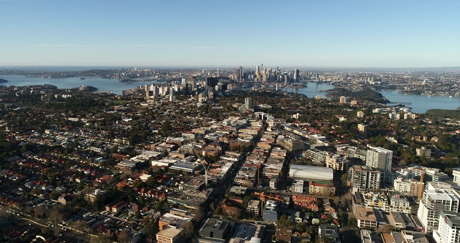 Lowering forward over local streets with residential houses facing high-rise apartment and business towers of North Sydney and CBD.