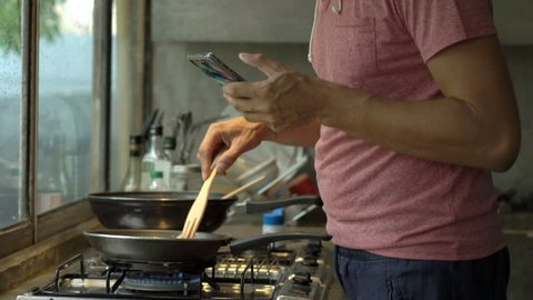 Young man using smartphone while cooking meal in kitchen