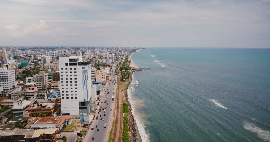 Drone flying over beautiful coastline of Colombo, Sri Lanka. Amazing aerial view of busy city street and ocean waves. #1014596288