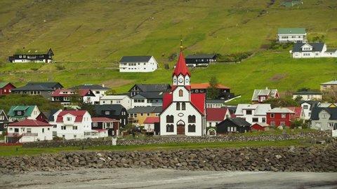 View of the Sandavagur town and Sandavagur Evangelical Lutheran Church, Island of Vagar, Faroe Islands.  Pan Left