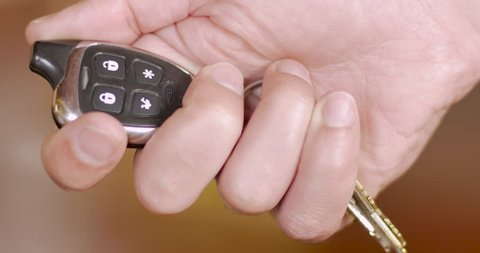 Man disarming and turning off a car alarm with a wireless remote control - close up