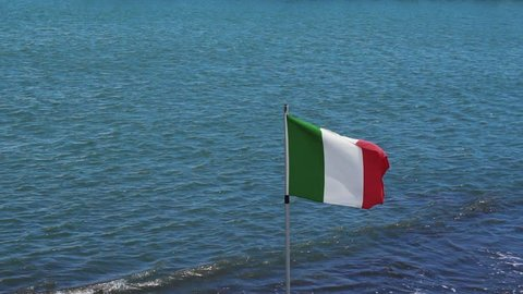 Italian flag waves in the wind near the sea, slow motion