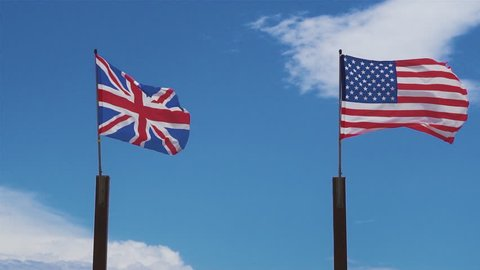 British and American flags wave in slow motion with the sky as a background