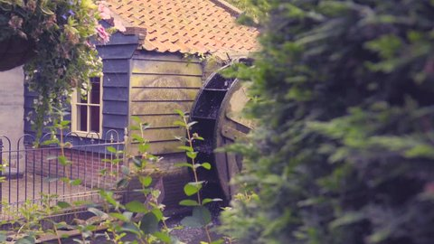 4K dolly shot of water wheel with plants in foreground.