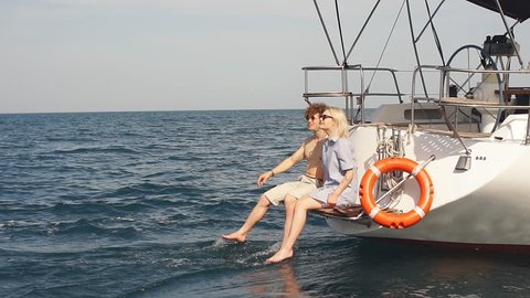 Vacation on a sailing yacht. Loving couple relaxing on a yacht. Young people spend a weekend on a yacht tour. Slow motion