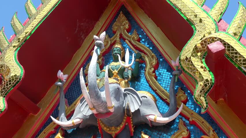 Sculpture of Hindu god Indra sitting on three-headed elephant Airaavatha decorating facade of Wat Phra Yai, Koh Samui island, Thailand. Decoration of temple exterior depicting Buddhist guardian deity.