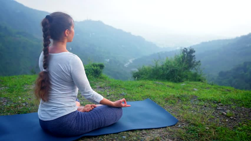 Woman doing yoga - meditating in Padmasana (Lotus Pose) outdoors in mountains on sunset | Shutterstock HD Video #1014692618