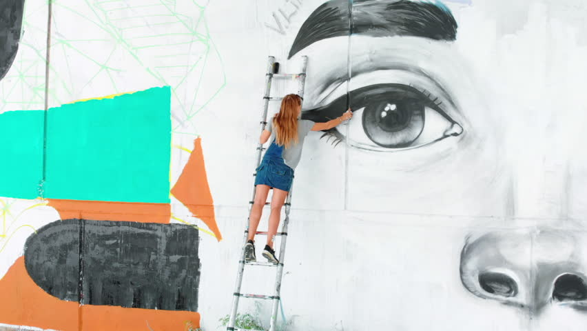 Beautiful girl making graffiti of big female face with aerosol spray on urban street wall. Cinematic toned footage. Creative art. Talented student in denim overalls drawing picture.