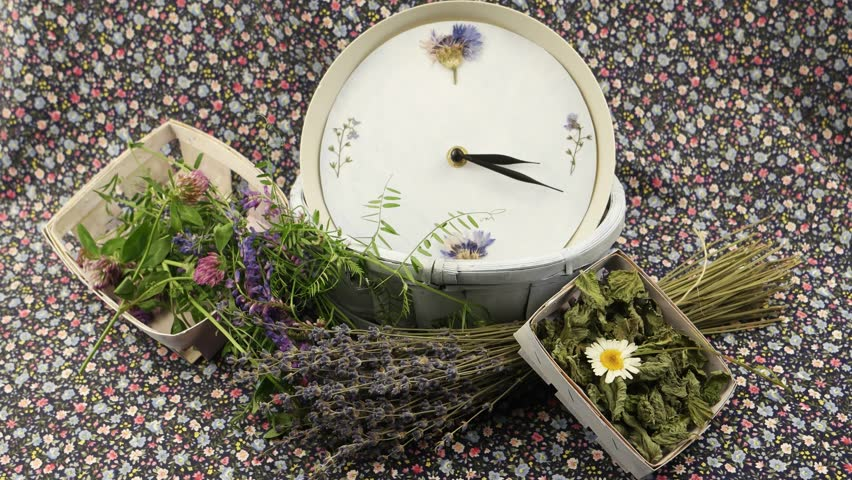 A clock in a blue wicker basket,  small bouquet of wild flowers in the wicker boxes and dried lavender against the background of fabric with a floral pattern, floristic composition