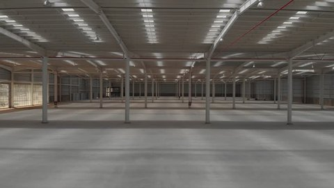 Aerial interior clip of an empty warehouse with camera moving backwards