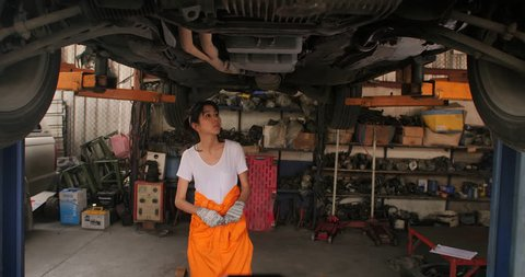 Young beautiful car mechanic inspects the car undercarriage way in garage, car service concept. dolly shot
