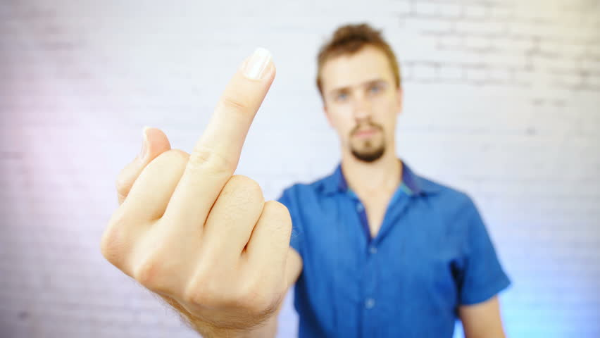 Angry man show the middle finger 4K. Middle shot of man out of focus lifting up a hand with middle finger showing fuck off in focus.