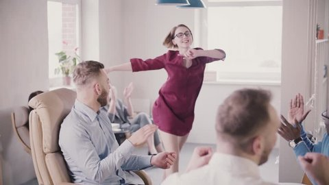 Happy Caucasian female boss doing victory dance, giving high-fives to multi-ethnic office colleagues, laughs slow motion