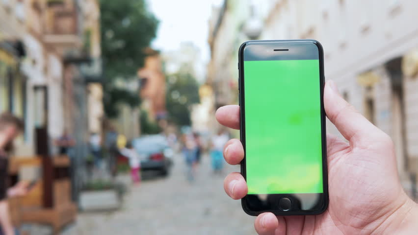 Male hand holding vertical black smartphone with green screen chroma key for tracking motion on the blurred city street background in sunny day. Close-up shot filmed in 4k UHD Slow motion | Shutterstock HD Video #1014760358