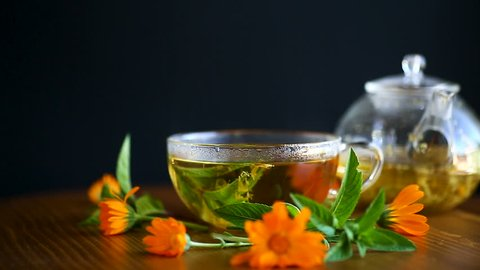 curative fresh hot tea with calendula flowers in a cup