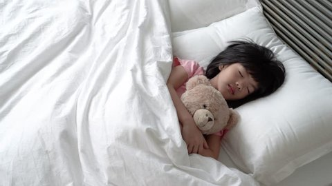 Asian adorable girl sleeps quietly and holding her cute fluffy teddy bear.