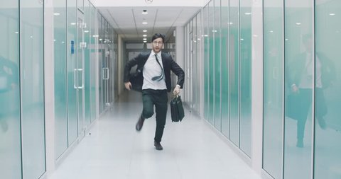 South asian businessman running down office hall. Office worker is late for work and hurrying with briefcase in hand. 4k