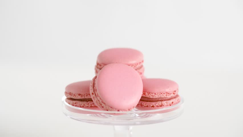sweets, pastry and food concept - pink macarons on glass confectionery stand over white background
