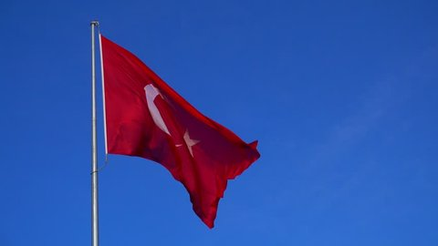 Turkish flag against blue sky.