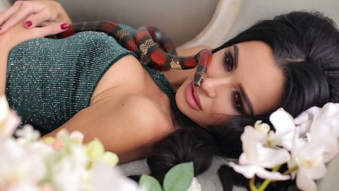 A gorgeous sexy girl is lying on a couch among the bouquets of flowers and a snake creeps along it. Portrait of a young woman with a snake.