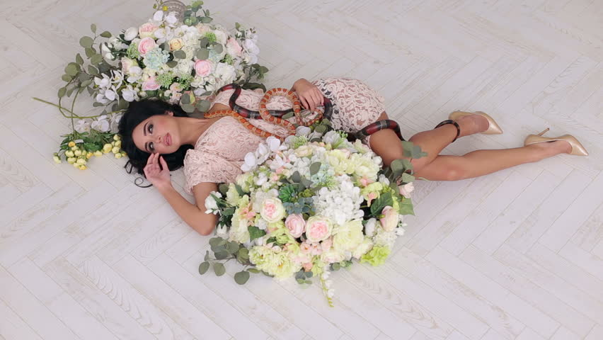 A sexy girl lies on the floor among large bouquets of flowers and two snakes creep along it. Beautiful girl holds a snake in hands on a white background. Wide shot.