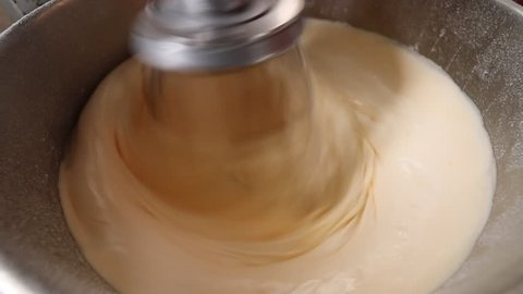 Mixing butter, flour, and egg as ingredients for making cakes in a stand mixer.An industrial kitchen food mixing machine whipping and mixing sweet creamy fluffy light cake mixture,