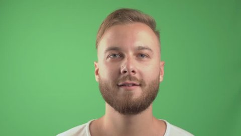 handsome bearded man smiling and looking and talk at the camera. Green screen background