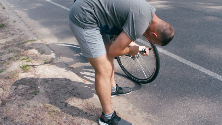 young man in the gray t-shirt sweating and inflating the tyre on woman's bycicle at the park in the morning