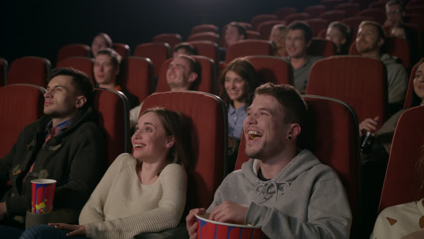 Young people laugh at comedy movie in cinema theatre. Young people laughing at cinema watching amusing comedy. Cheerful people watching comedy film in slow motion