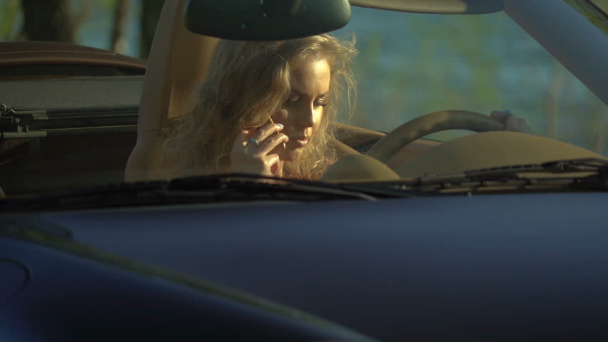 Young pretty blonde woman talking on her phone in her brand-new car with modern inside and leather seats. | Shutterstock HD Video #1014888778